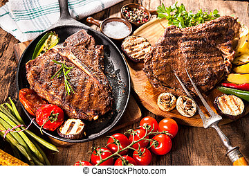 Beef steaks with grilled vegetables and seasoning on wooden...