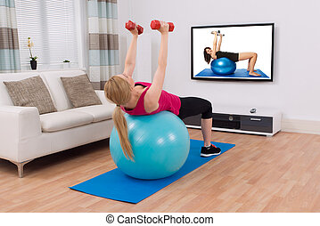 Woman Exercising With Fitness Ball And Dumbbell - Young...