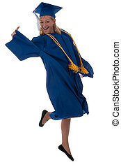 Happy graduate - Teen girl in a graduation gown jumping for...