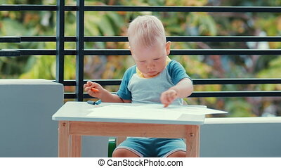 Toddler boy practice to paint with crayons on paper sitting...