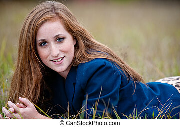 Red-headed teen girl lying in grass - Pretty red-headed teen...