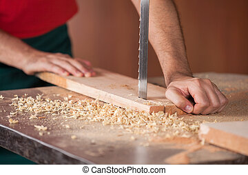 Carpenter's Hands Cutting Wood With Bandsaw - Cropped image...