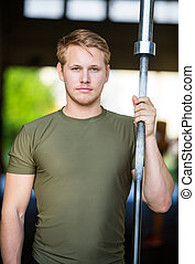 Athlete Holding Barbell Bar At Gym - Portrait of confident...