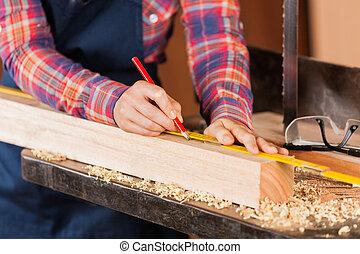 Female Carpenter Marking Wood With Pencil