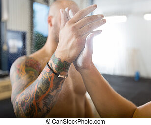 Athletes Giving High-Five At Gym - Young male athletes...