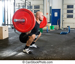 Male Athlete Lifting Barbell At Gym - Full length young male...