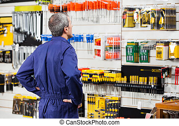 Worker With Hands On Hip In Hardware Store - Rear view of...