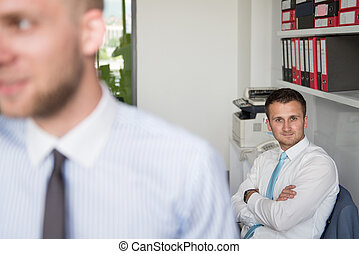 Businessman Talking On Telephone In Office - Happy Young...