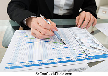 Businesswoman Working On Gantt Chart - Close-up Of...