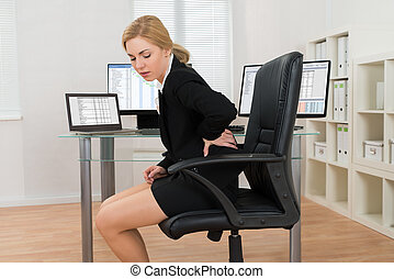 Businesswoman Suffering From Backache In Office - Young...