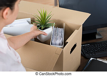 Businesswoman Packing Belongings In Cardboard Box - Young...