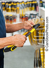 Salesman Holding Hacksaw In Store - Midsection of senior...