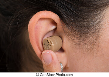 Woman Ear With Hearing Aid - Close-up Of Woman Ear Wearing...