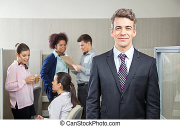 Confident Manager With Employees Discussing In Background -...