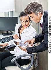 Manager Using Tablet Computer With Customer Service Agent