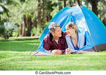 Couple Looking Each Other At Campsite - Smiling couple...