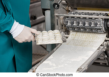 Chef Holding Ravioli Pasta Tray By Machinery - Midsection of...