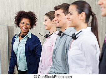 Happy Female Call Center Employee Standing With Team -...
