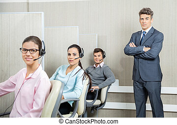 Confident Businessman Standing By Team In Call Center -...