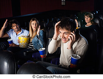 Spectators Shouting Man Using Mobilephone In Theater -...