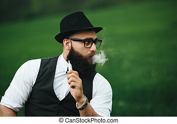 man with a beard smokes electronic cigarette - Man with a...