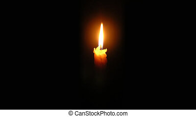 Candle is burning on the black