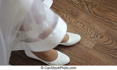 bride wears white shoes at wedding