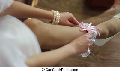 bride dresses garter on her leg