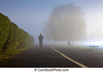 Man at urbanized path during misty weather - Walking man on...