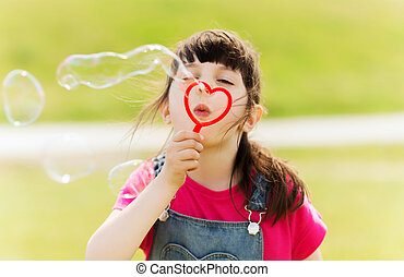 little girl blowing soap bubbles outdoors - summer,...