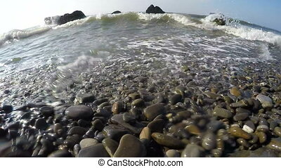 Slow motion of splashing waves on a wild pebble beach of...