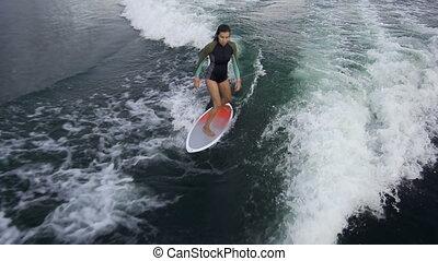 Balancing on Waves - High angle of a girl wake surfing