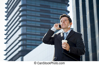 young attractive businessman in suit and tie talking on...