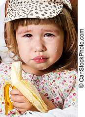 Girl eating a banana - Crying girl eating a banana