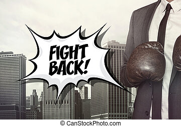 Fight back text with businessman wearing boxing gloves on...