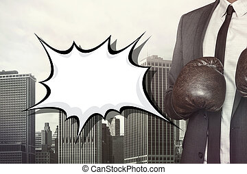 Empty speech bubble with businessman wearing boxing gloves...
