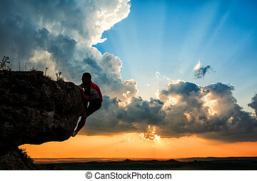 One guy sits on a rocknd looking at sunset