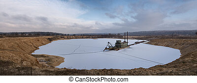suction dredge in open pit in winter
