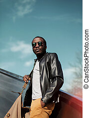Fashion elegant young african man wearing a black leather jacket with bag in the city over evening sky