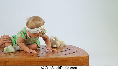 Child Sits On The Table - A small child sits on the edge of...