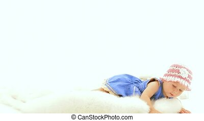 The baby girl is lying on a white background