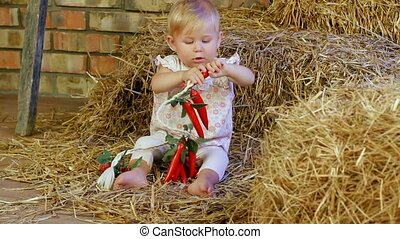 Child Plays With Toys - Little girl sits on a farm in a...
