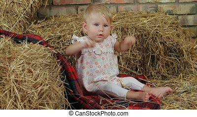 Child On The Farm - A small child sitting on a haystack.