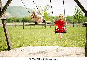 girls in swing - little blond girls swinging outdoor
