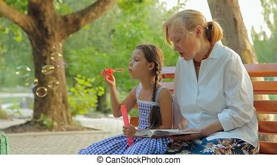 Seating In A Park - Grandmother and granddaughter spending...