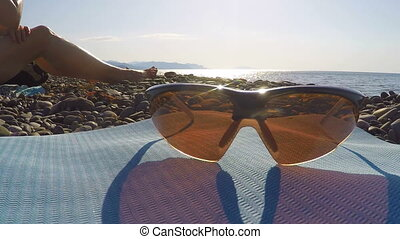 Polarized sports cycling sunglasses on wild beach in summer