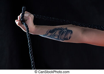 Photo woman's hand with whip and tattoo