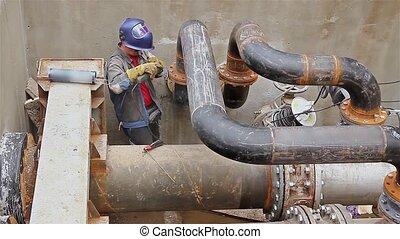 Manhole, metalworker is grinding - Metal worker is grinding...