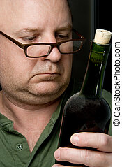 Wine Connoisseur - A Wine Connoisseur inspecting a bottle of...