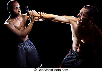 Self Defense Against A Gun - Martial artist disarming a...